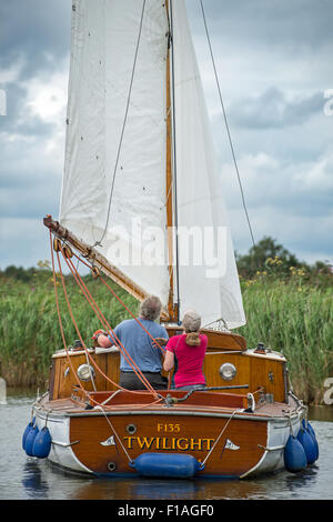 A couple sail a Norfolk Broads sailing boat down through one of the dykes on the way from Potter Higham to Hickling - Stock Photo