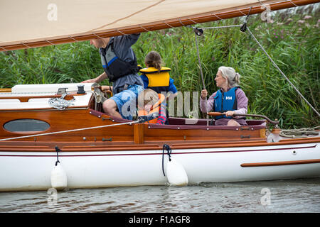 A family sail a Norfolk Broads sailing boat down through one of the dykes on the way to Potter Higham - Stock Photo
