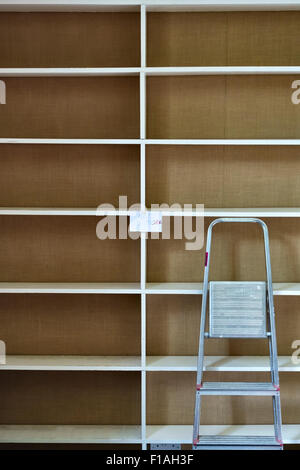 Moving house - empty bookshelves and a stepladder - Stock Photo