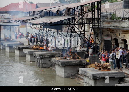 Hindu cremation rituals at the banks of Bagmati river at Pashupatinath Temple in Kathmandu - Stock Photo