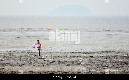 A young girl walking back from a muddy shoreline on an overcast day at a typical english seaside resort. she's covered - Stock Photo
