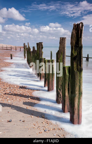 Old wooden breakwater groynes on a sunny day at Winchelsea Beach, East Sussex - Stock Photo