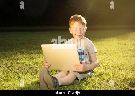 Portrait of little boy sitting on a meadow with laptop - Stock Photo