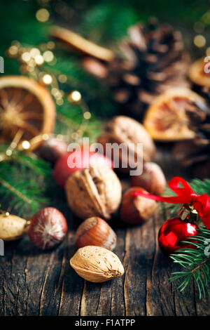 Different nuts with christmas decorations on wooden background - Stock Photo