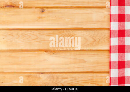 Red towel over wooden kitchen table. View from above with copy space - Stock Photo