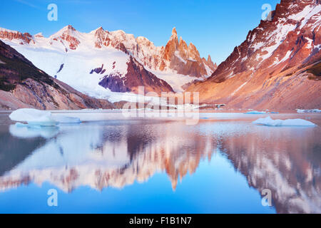 The peaks of Cerro Torre in Argentinian Patagonia reflected in the lake below. Photographed at sunrise. - Stock Photo