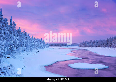 A rapid in a river in winter at sunrise. Photographed at the Äijäkoski rapids in the Muonionjoki river in Finnish - Stock Photo