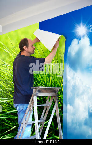 man putting up wallpaper for Changing of scenery. - Stock Photo