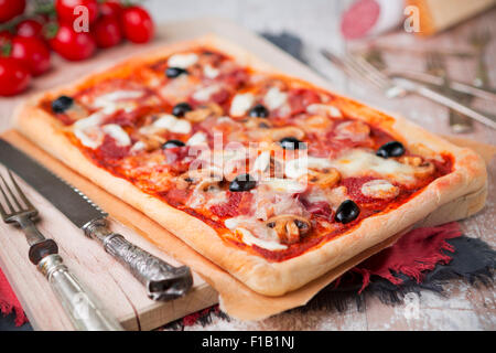 Homemade rectangular pepperoni pizza on a rustic table with ingredients. - Stock Photo