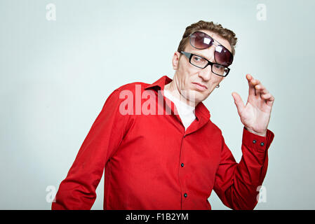 amazed man in red shirt with two pairs of eyeglasses - Stock Photo