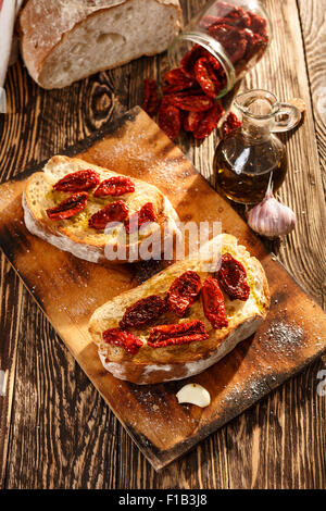 Bruschetta with dried tomatoes, garlic and olive oil. Traditional Italian cuisine sandwich made of grilled ciabatta. - Stock Photo
