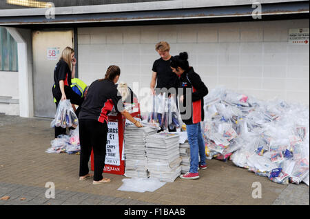 Promotion staff from east Anglian daily Times and Ipswich Star with copies of newspaper Goody bags at football match - Stock Photo