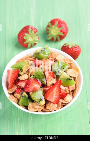 Granola with fresh strawberry and kiwi in white bowl on green table - Stock Photo