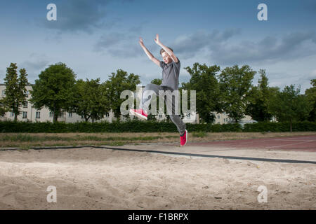 frozen side frontal full body view of a male young teenagers jumping into a long jump pit - Stock Photo
