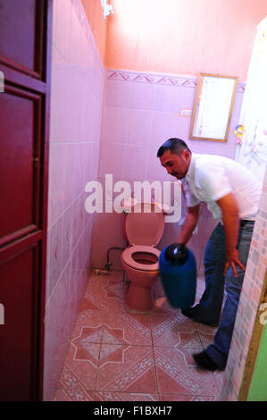 Guatemala, Concepcion las Minas, father using and cleaning bathroom (Doel Fransuath Fernández Trujillo, 28 years) - Stock Photo
