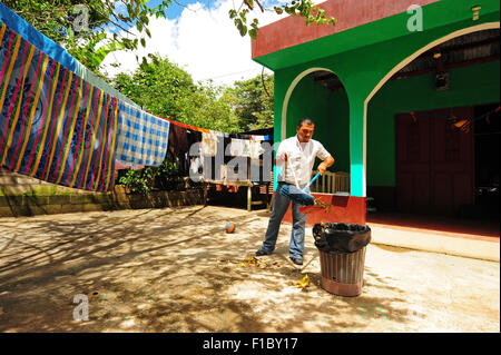 Guatemala, Concepcion las Minas, father cleaning and using trash in patio (Doel Fransuath Fernández Trujillo, 28 - Stock Photo