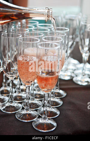 Pink champagne being poured into champagne flutes - Stock Photo