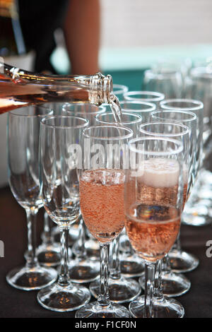 Pink champagne being poured in champagne glasses - Stock Photo