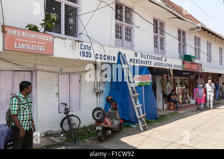 Warehouse building and pedestrians in Jew Town, Kochi, India. Note the Hindu swastikas decorating the window grilles - Stock Photo
