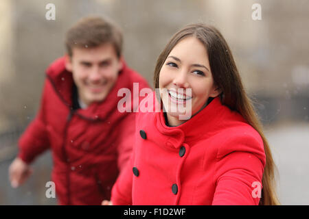 Happy couple wearing red jackets running towards camera in winter - Stock Photo