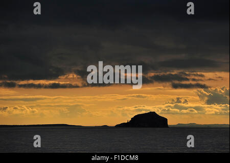 Bass Rock and its lighthouse at sunset with rain clouds, Firth of Forth, East Lothian, Scotland, UK - Stock Photo