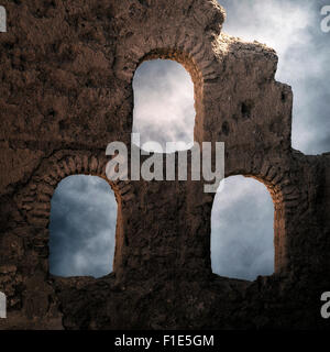 three windows in an old stone wall - Stock Photo
