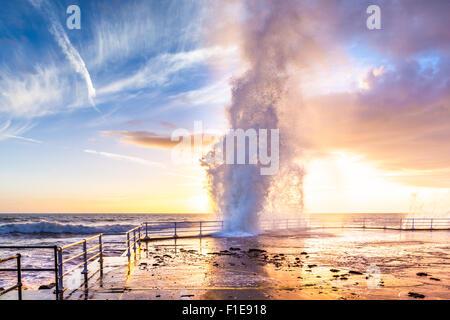Big wave splashing against the promenade at sunset - Aberystwyth Ceredigion Mid Wales UK - Stock Photo