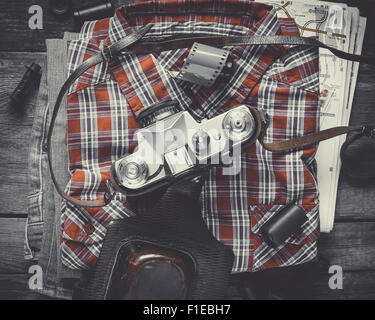 Plaid shirt, pair of jeans and old film camera. Top view. Vintage stylized. - Stock Photo