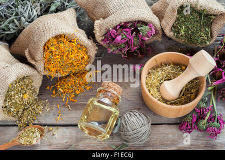 Healing herbs in hessian bags, wooden mortar with chamomile and essential oil on rustic table, herbal medicine. - Stock Photo