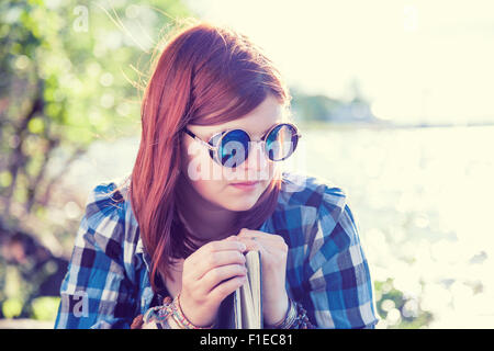 Pensive beautiful young woman in sunglasses with book near river - Stock Photo