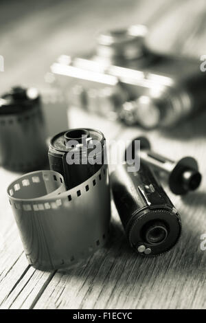 Old photo film rolls, cassette and retro camera on background. Black and white stylized. - Stock Photo