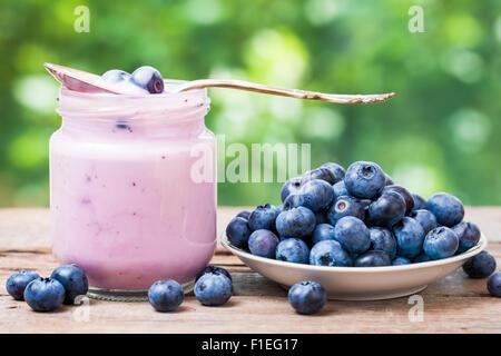 Fresh blueberries yogurt in glass jar and saucer with bilberries. - Stock Photo