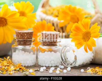 Three bottles of homeopathy globules and marigold flowers. - Stock Photo