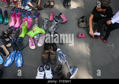 Berlin, Germany. 1st Sep, 2015. Children try used shoes at the reception center for refugees and asylum-seekers - Stock Photo