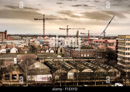 View from top of Cliffords Tower, York: Construction cranes on York skyline with snow covered hills in distance - Stock Photo