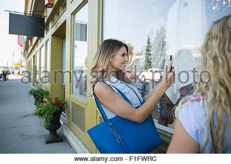 Woman photographing window display at storefront - Stock Photo