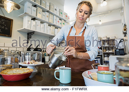 Bakery owner pouring tea at counter - Stock Photo