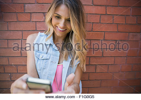 Smiling blonde woman texting with cell phone - Stock Photo