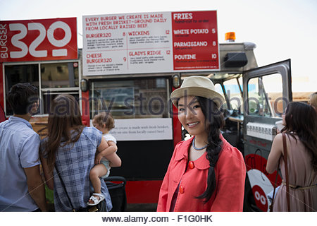 Portrait smiling woman in hat outside food truck - Stock Photo