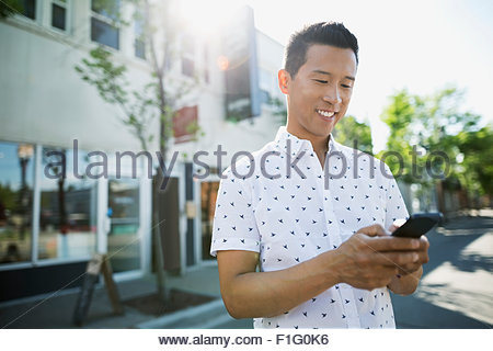 Smiling man texting with cell phone on sunny street - Stock Photo