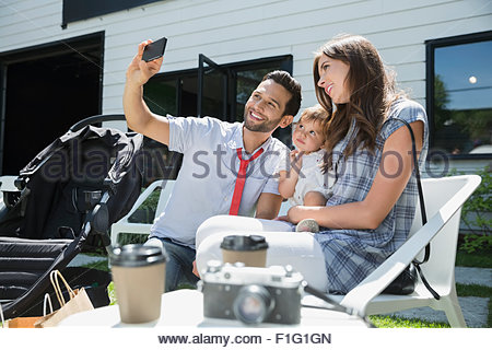 Family taking selfie with camera phone cafe patio - Stock Photo