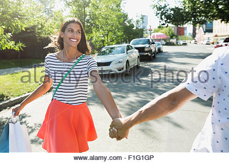 Smiling couple holding hands and crossing sunny street - Stock Photo
