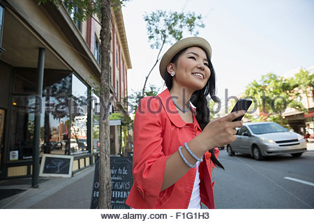 Smiling woman with cell phone on city street - Stock Photo