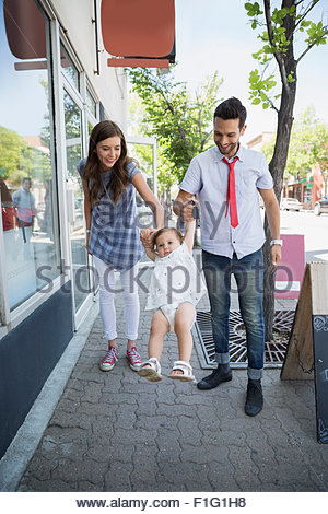 Parents swinging baby daughter on sidewalk - Stock Photo