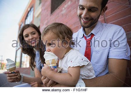 Baby girl sticking face soft serve ice cream - Stock Photo