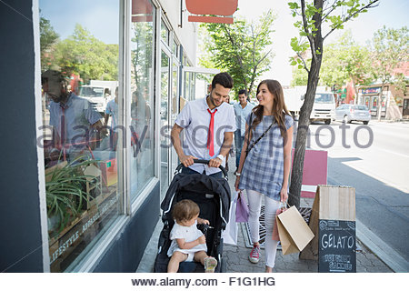 Family with shopping bags on sidewalk at storefront - Stock Photo