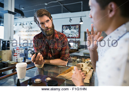 Worker explaining after shave spray to customer shop - Stock Photo