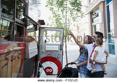 Family outside food truck on sidewalk - Stock Photo