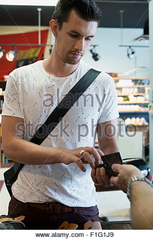 Man paying with credit card in shop - Stock Photo