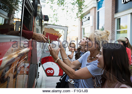 Customers receiving food outside food truck - Stock Photo